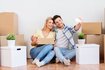 moving, people and real estate concept - smiling couple with big cardboard boxes taking selfie by smartphone at new home