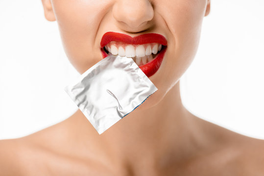 cropped shot of young woman holding condom in teeth isolated on white
