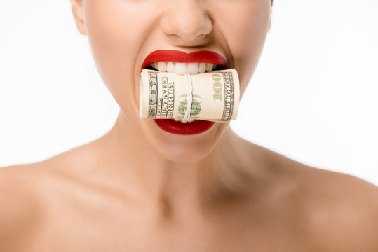 cropped shot of woman holding rolled dollar banknotes in teeth isolated on white