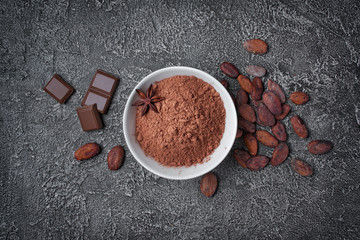 .Top view of cocoa powder in white bowl with pieces of chocolate bar and cocoa beans