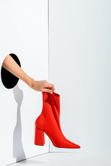 cropped image of girl holding red stylish high heel in hand through hole on white