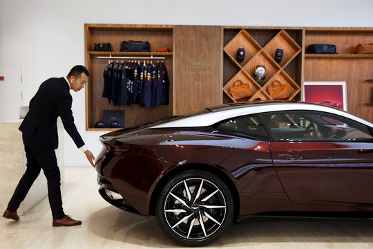 Sales representative opens the boot of an Aston Martin luxury sports car as he poses for a picture at a dealership in Beijing