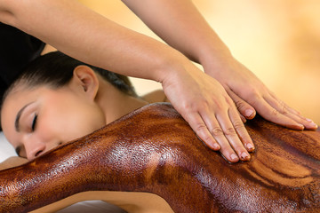 Papiers peints Chocolat Spa therapist applying curative hot chocolate on woman.