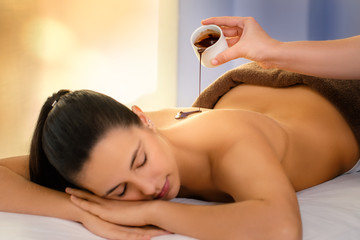 Therapist pouring hot chocolate massage oil on young woman.