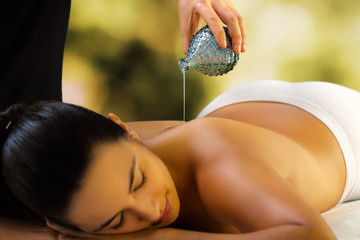 Therapist pouring massage oil on woman's back.