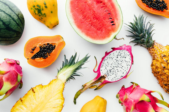 Flat lay tropical fruit layout made of dragon fruit, watermelon, papaya and pineapple on a white background, creative summer food concept
