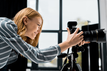 side view of smiling young female photographer working with professional photo camera in studio