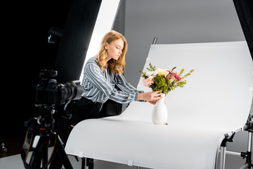 close-up view of photo camera and young woman arranging flowers in photo studio