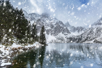 Winter at Eye of the Sea lake in Tatra mountains with falling snow, Poland