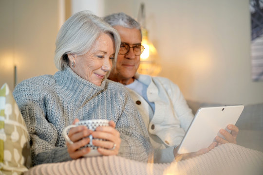 Senior couple relaxing at home on couch with tablet