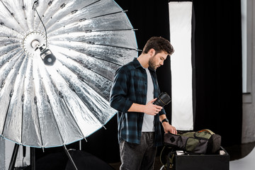 handsome young photographer holding lens and looking into backpack in photo studio