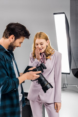 happy young photographer and model using photo camera together in studio