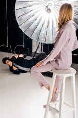 young photographer with camera lying and photographing beautiful model in studio