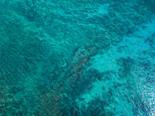 Aerial view of the tropical sea surface with coral reefs on the bottom