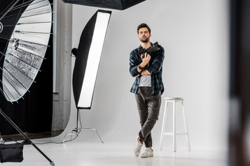 full length view of confident young photographer holding professional camera and looking at camera in photo studio Wall mural
