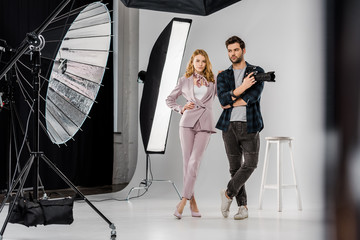 young photographer camera and beautiful female model standing together in photo studio
