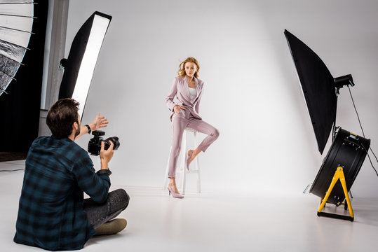 young photographer shooting beautiful stylish young woman in photo studio
