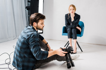 young photographer showing camera to beautiful female model in photo studio
