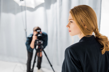 close-up view of beautiful young model and photographer working behind in studio