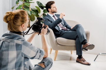 back view of young female photographer photographing handsome businessman in studio