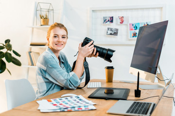 beautiful young female photographer smiling at camera while working in office
