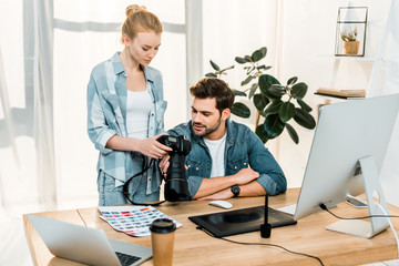 professional young photographers using photo camera and discussing photos in office