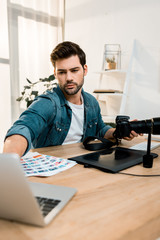 handsome young photographer using camera and laptop at workplace