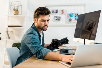 handsome young photographer holding camera and using laptop in office