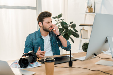 serious young retoucher talking by smartphone and using desktop computer with drawing tablet at workplace