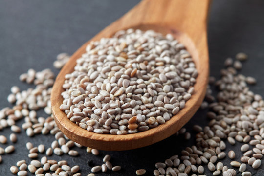 Close up of white chia seeds in wooden spoon