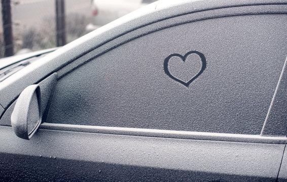 heart symbol on frozen car window in winter