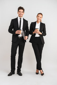 Full length of smiling young business couple walking