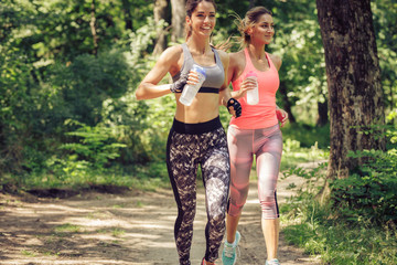 Two young female friends jogging trough the forest.Spring exercise and workout.
