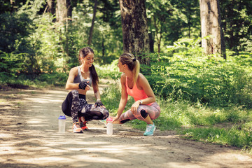 Two young woman stretching and relaxing after jogging and workout  outdoor.