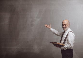 Obraz Smiling confident professor teaching and pointing at the blackboard - fototapety do salonu