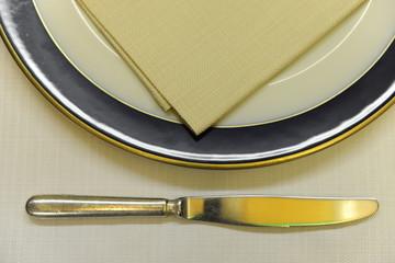 Piatto con coltello e tovagliolo sopra tavola gialla