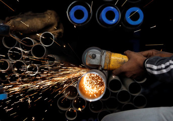 A worker cuts a metal pipe at a workshop in an industrial area in the old quarters of Delhi