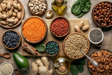 flat lay of legumes, superfoods and healthy ingredients on wooden board with rustic background