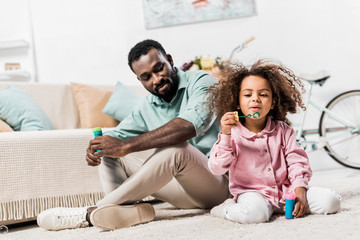 african american father and daughter making soap bubbles and sitting on floor