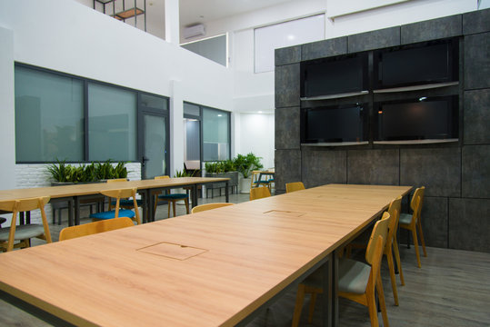 Modern conference hall with plasma displays and long tables. Green plants near wall.  Creative interior of business company concept