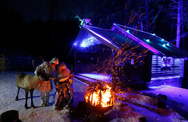 A man dressed as Father Frost and a woman dressed as his granddaughter Snegurochka sit near fire during the performance at the Royev Ruchey Park in the suburbs of Krasnoyarsk