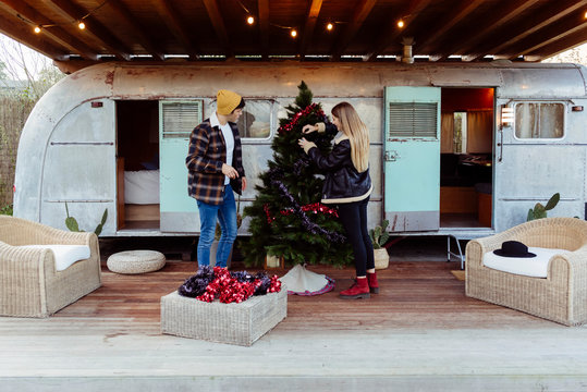Young couple decorating Christmas tree near trailer