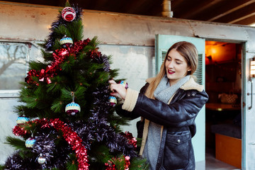 Young woman decorating Christmas tree near trailer