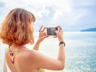 Beautiful asian woman with short hair using smart phone take a photo seascape view