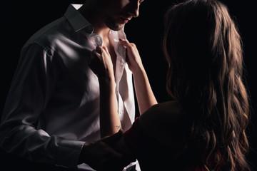 Obraz back view of woman undressing man shirt isolated on black - fototapety do salonu