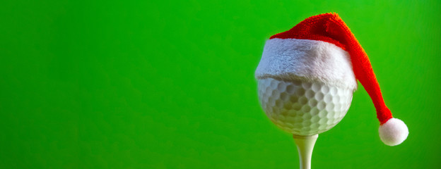 Foto auf Acrylglas Golf The golf ball mounted on the tee is wearing a Santa Claus souvenir hat. Blank for a postcard for a golfer to celebrate the New Year and Christmas. Bright green background. Copy space.