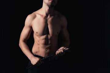 cropped view of shirtless man holding leather flogging whip isolated on black