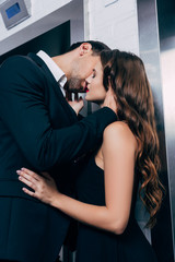 man in suit passionately kissing beautiful woman near elevator