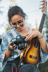 Smiling woman holding ukulele,  checking pictures on camere