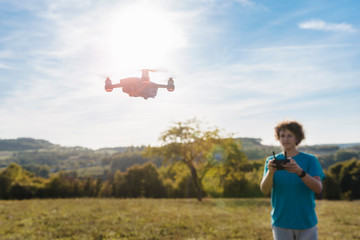 Boy navigating a flying drone outdoors Wall mural